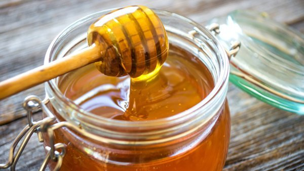 Honey dipper poised over honey jar
