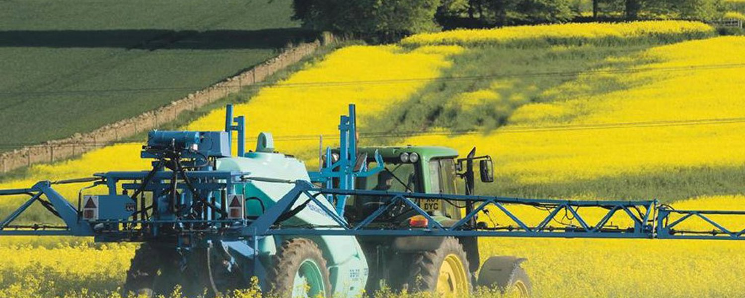 tractor spraying field of OSR