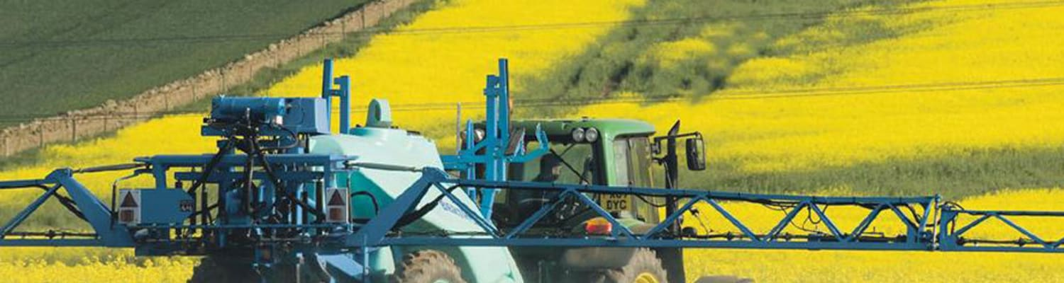 Spraying tractor moves through yellow crop